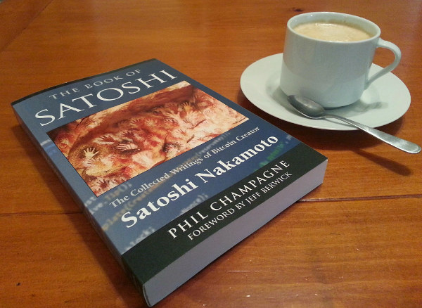 Photo of a softcover copy of the book next to a cup of coffee